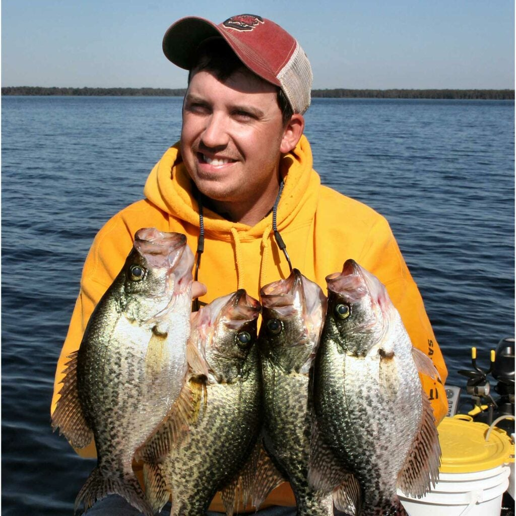 Angler holding up large black crappies.