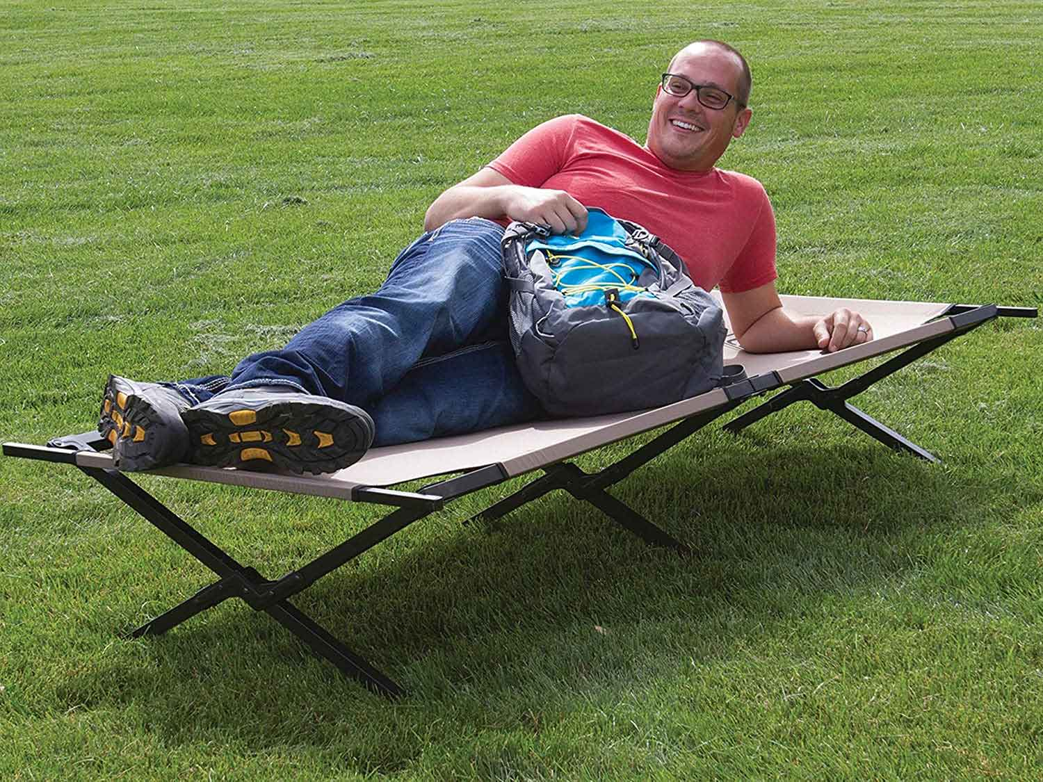 Man lying on a cot on the grass