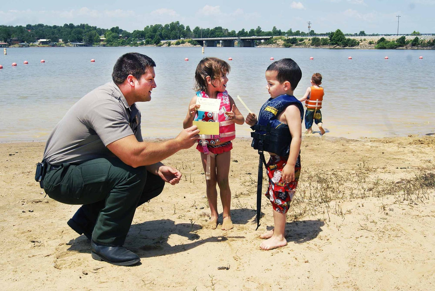 Man on a beach with two young children