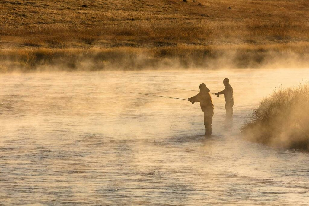 Two anglers fly fishing in the morning fog on a river.