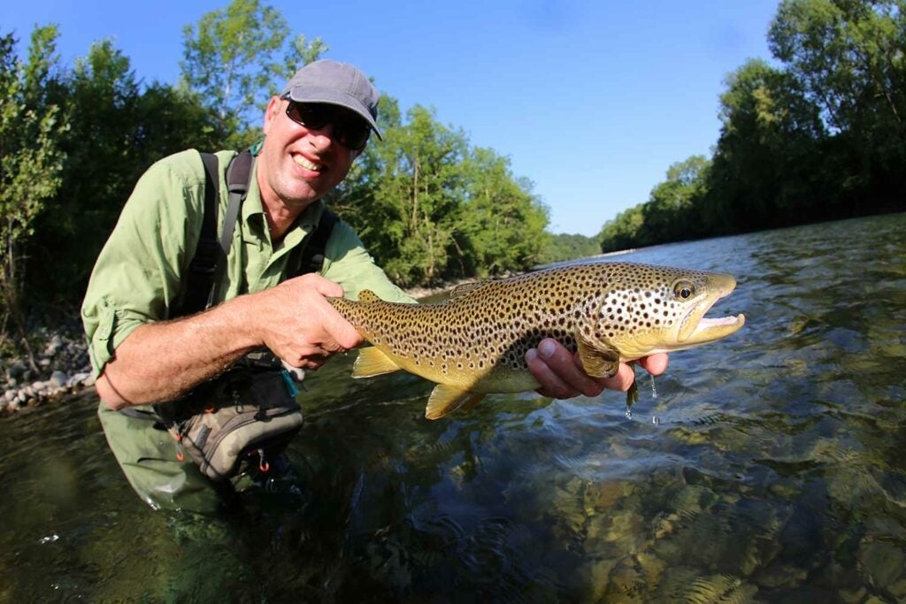 Angler holding up a large trout.