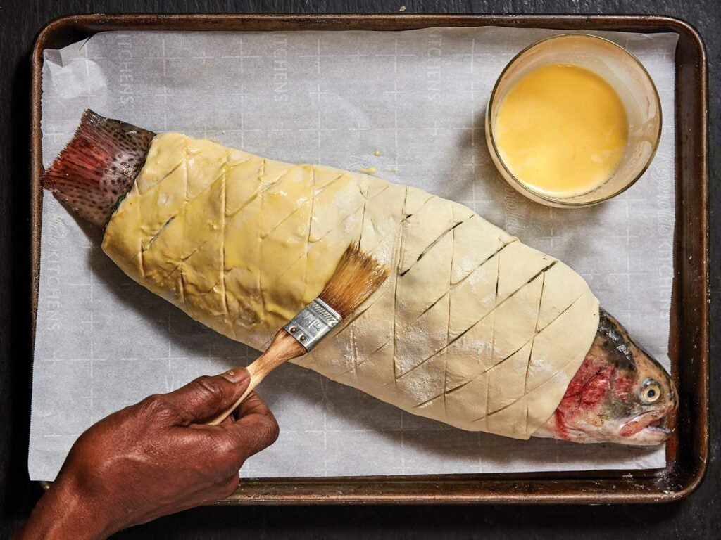 A steelhead trout wrapped in pastry dough being brushed with butter.