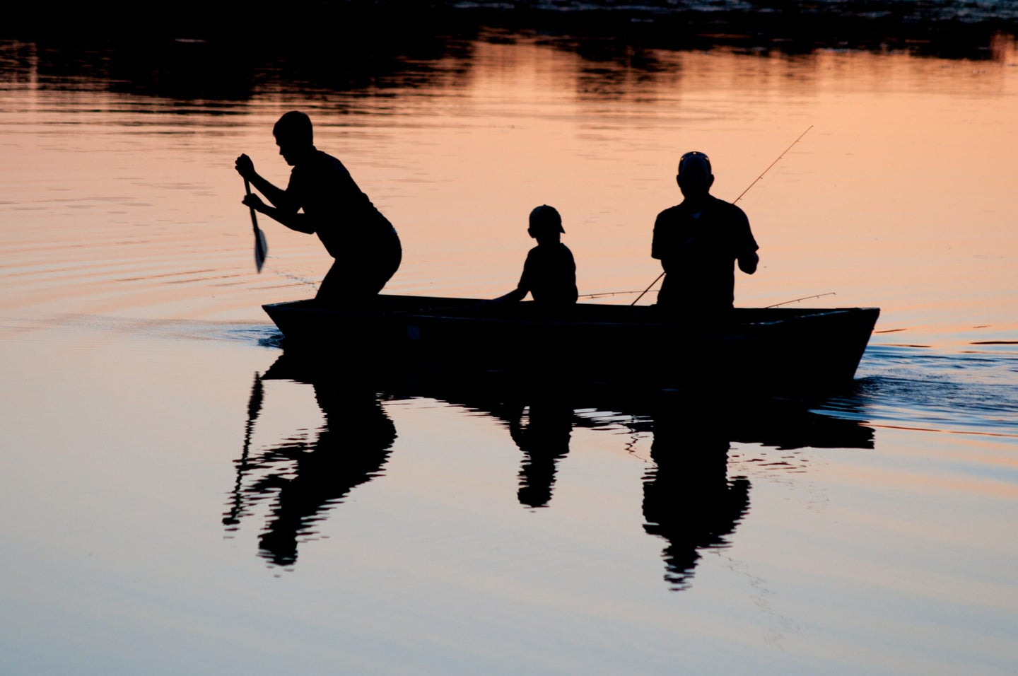 Three people in a boat at sunset.