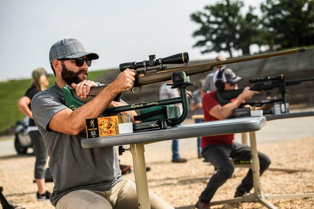Man aiming a 6.5 Creedmoor rifle at a shooting range.