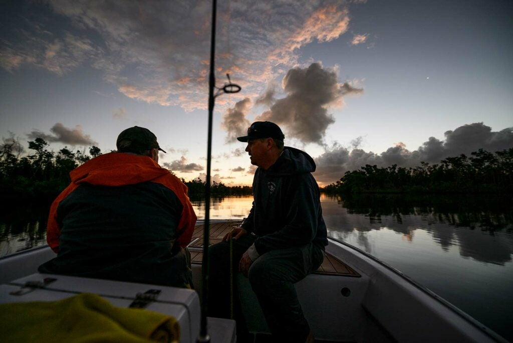Two anglers on a boat at sunset.
