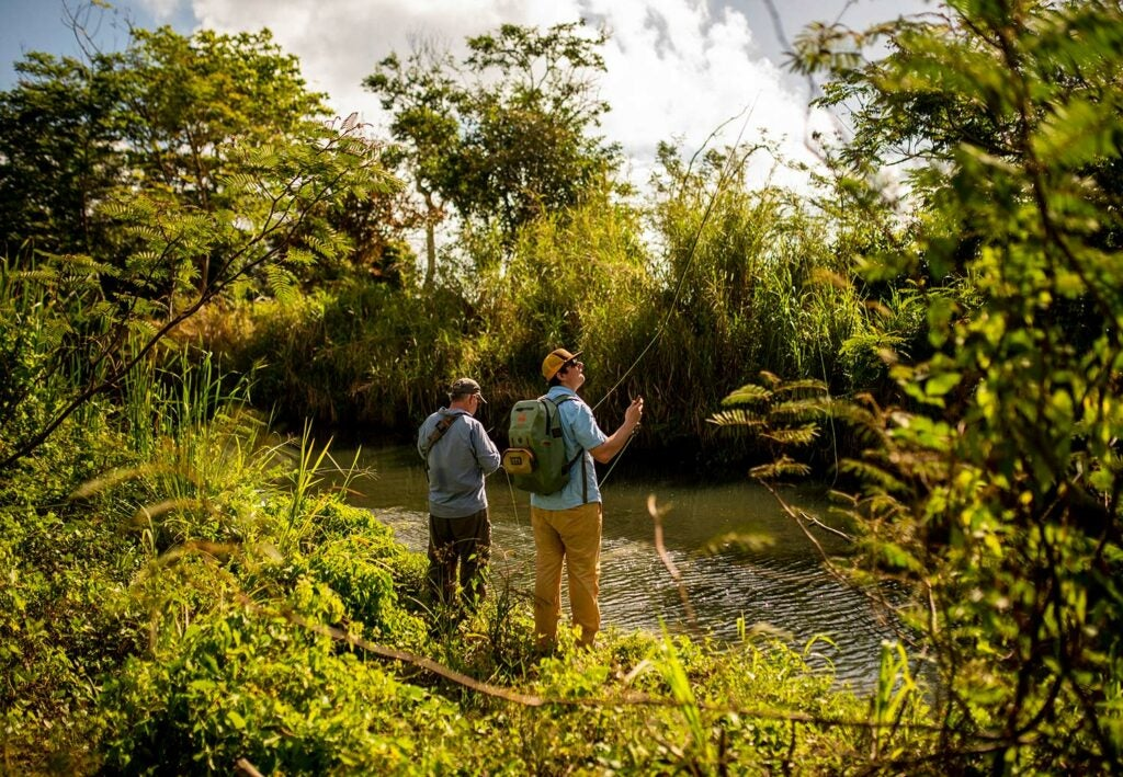 Two anglers standing on a river side.