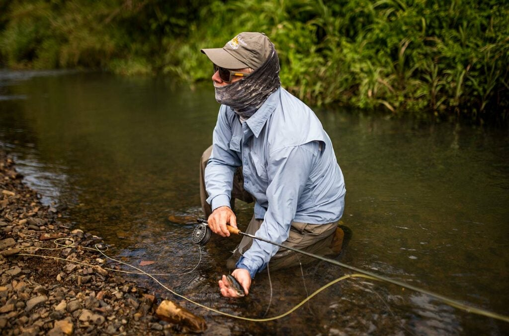 Angler kneeling by a river with a mountain mullet.
