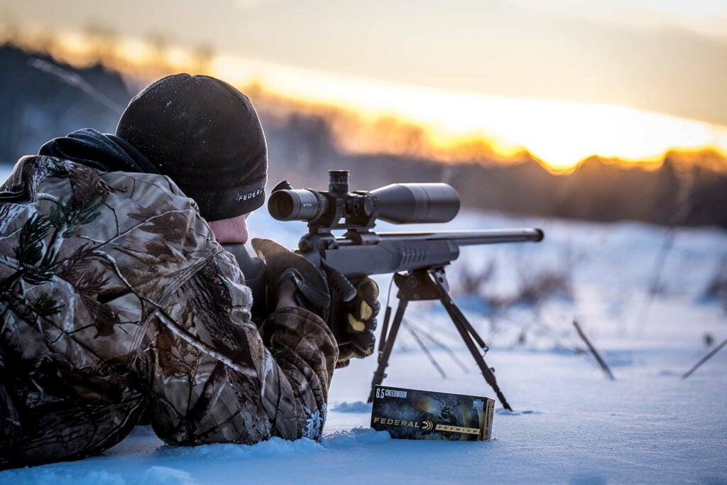 Hunter aiming a 6.5x55 Swede rifle in the snow.