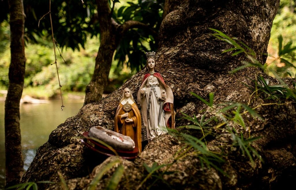 Statues of saints look over a river.