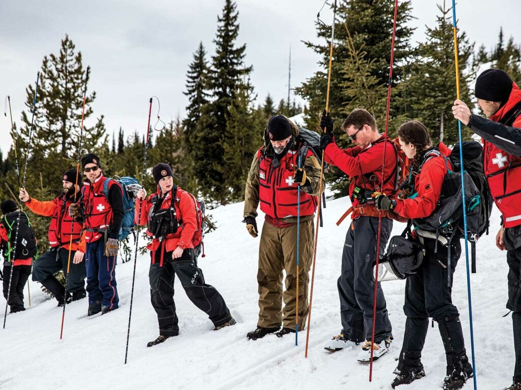A search and rescue team train with snow poles.