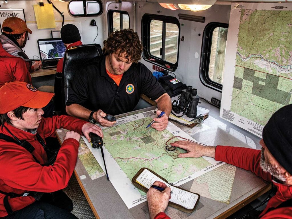 A search and rescue team study a map and coordinates.