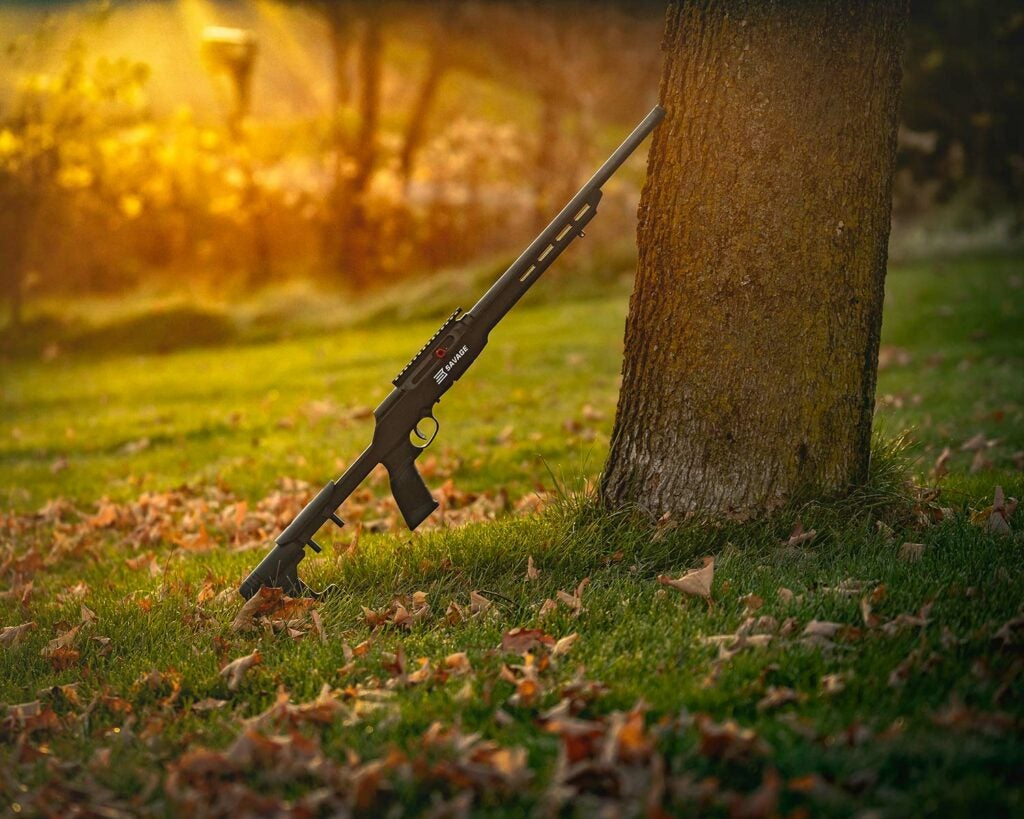 Savage Arms A22 Precision rifle leaning against a tree.