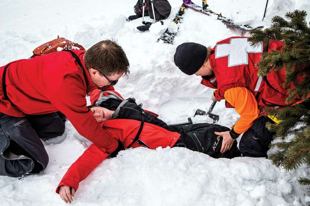 A search and rescue team pulls a person out of snow in training.