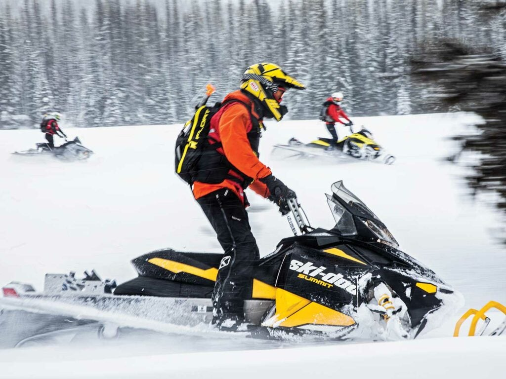 A team of search and rescue personnel riding snowmobiles.