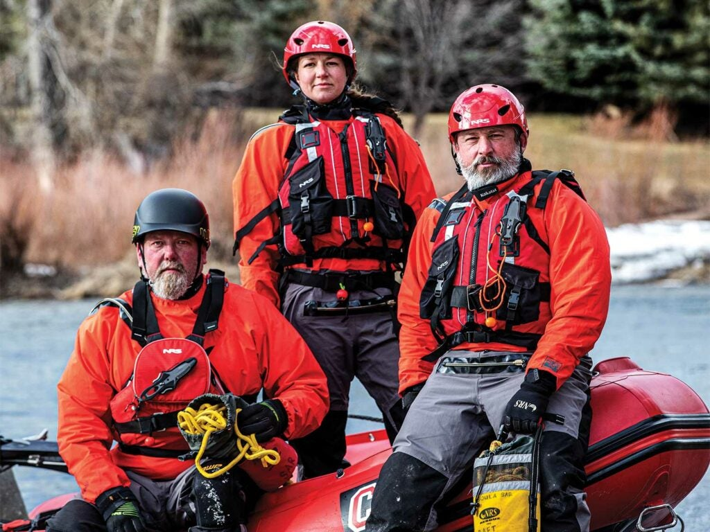 A search and rescue team near an inflatable Zodiak raft.