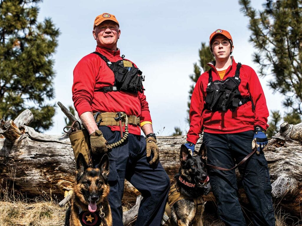 Two search and rescue team members with two German shepherd dogs.