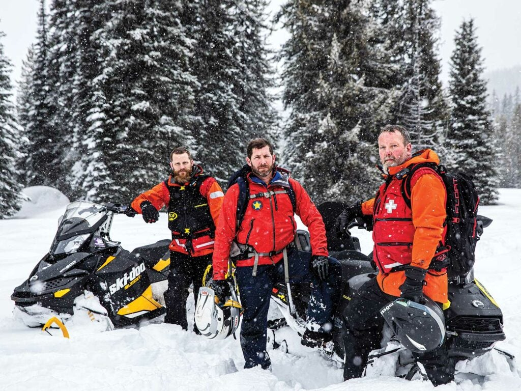A search and rescue team standing beside snowmobiles.