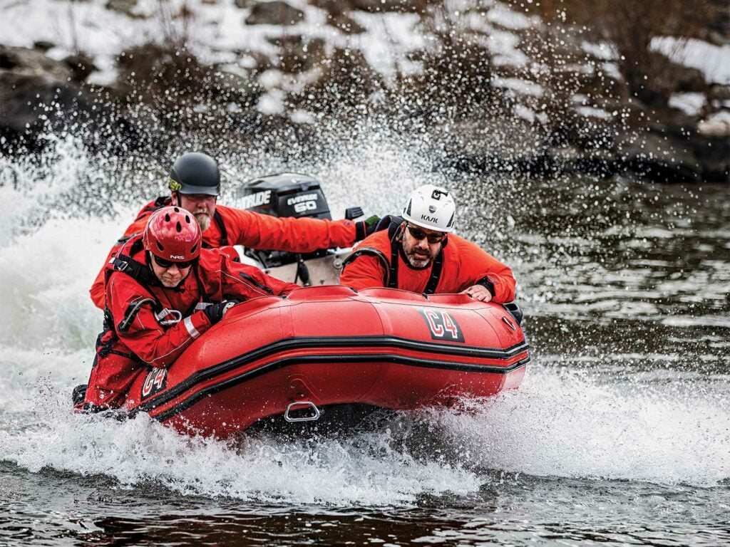 A search and rescue team on an inflatable zodiac on Clark Fork River.