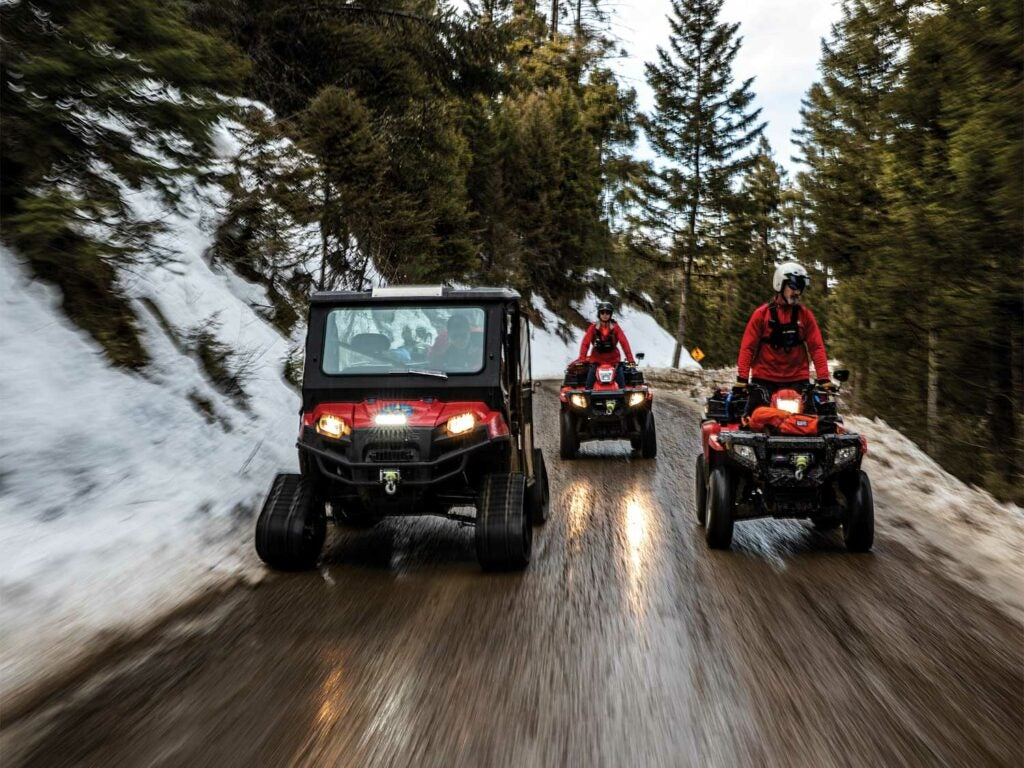 A team of search and rescue personnel drive a UTV and two ATVs down a road.