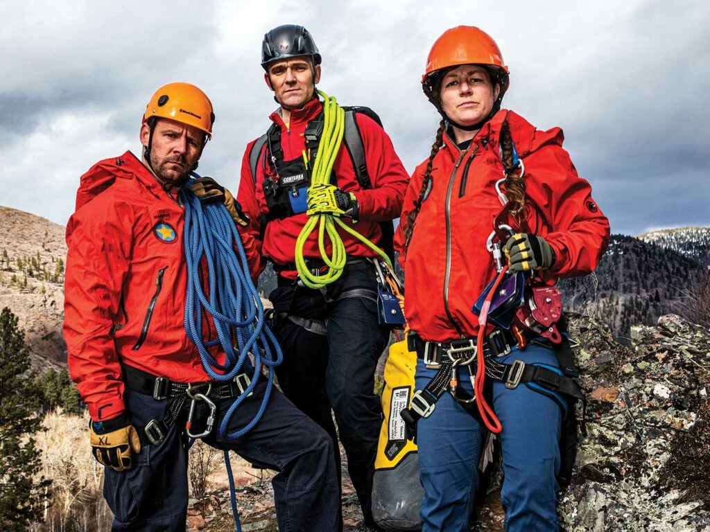 A team of search and rescue personnel with climbing equipment.