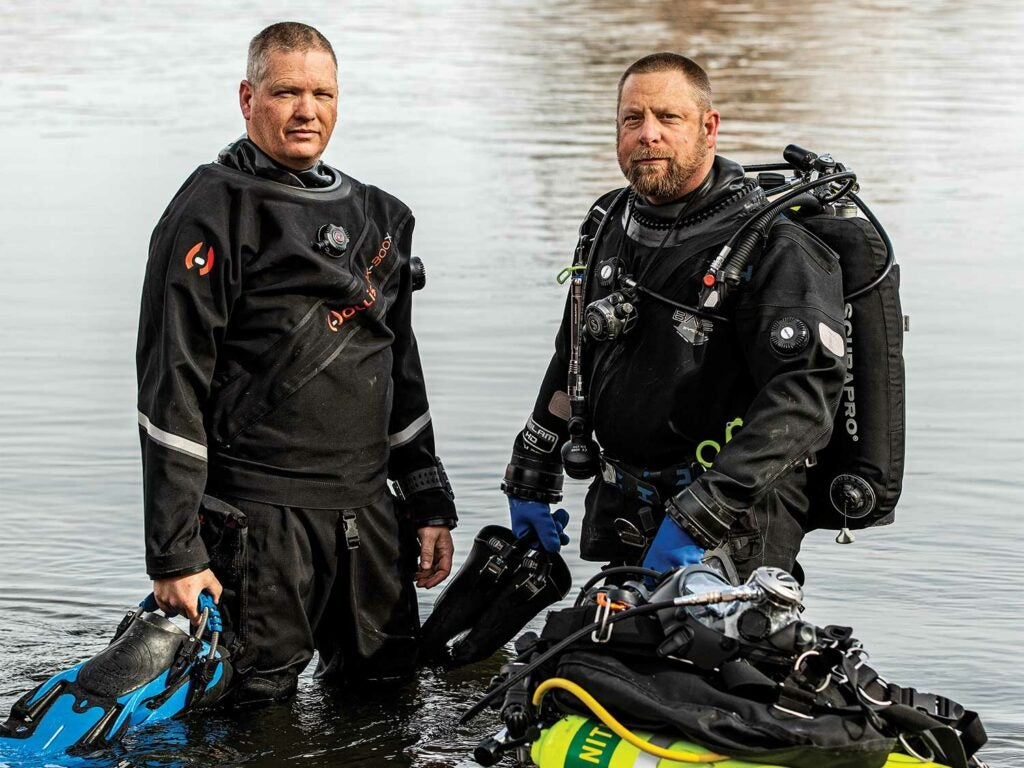 Two diving members of a search and rescue team prepare for a dive.