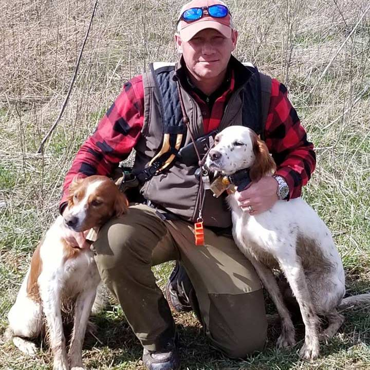 A hunter with two dogs.