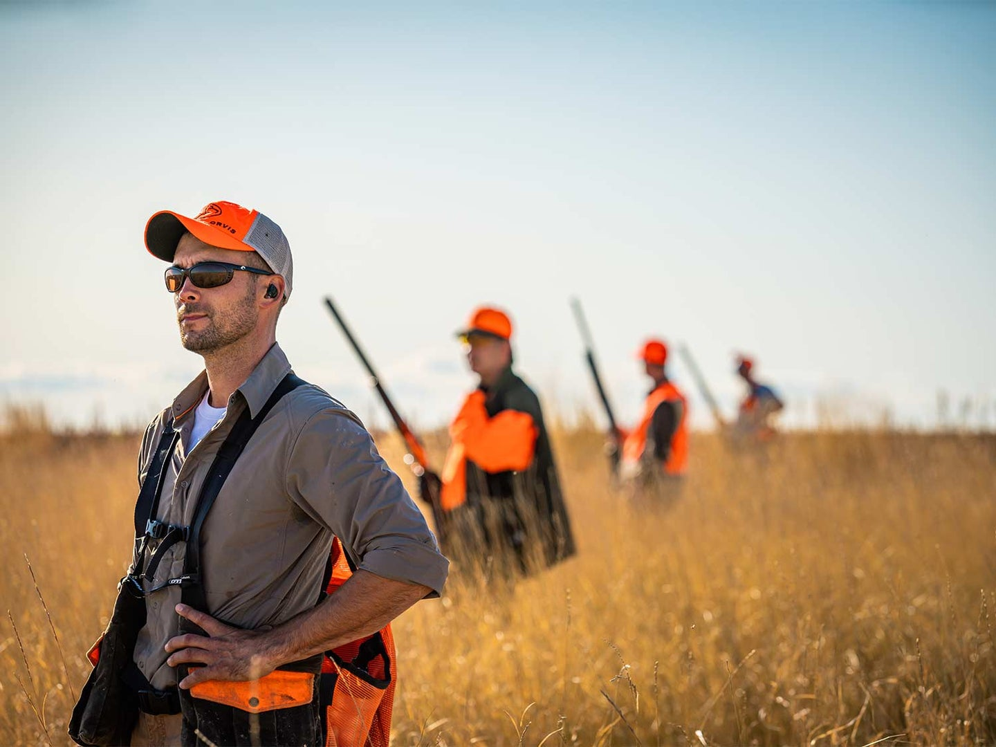 Hunters and guides standing in a brown field.
