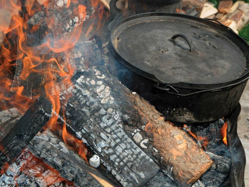 A cast-iron stove on a camp fire.