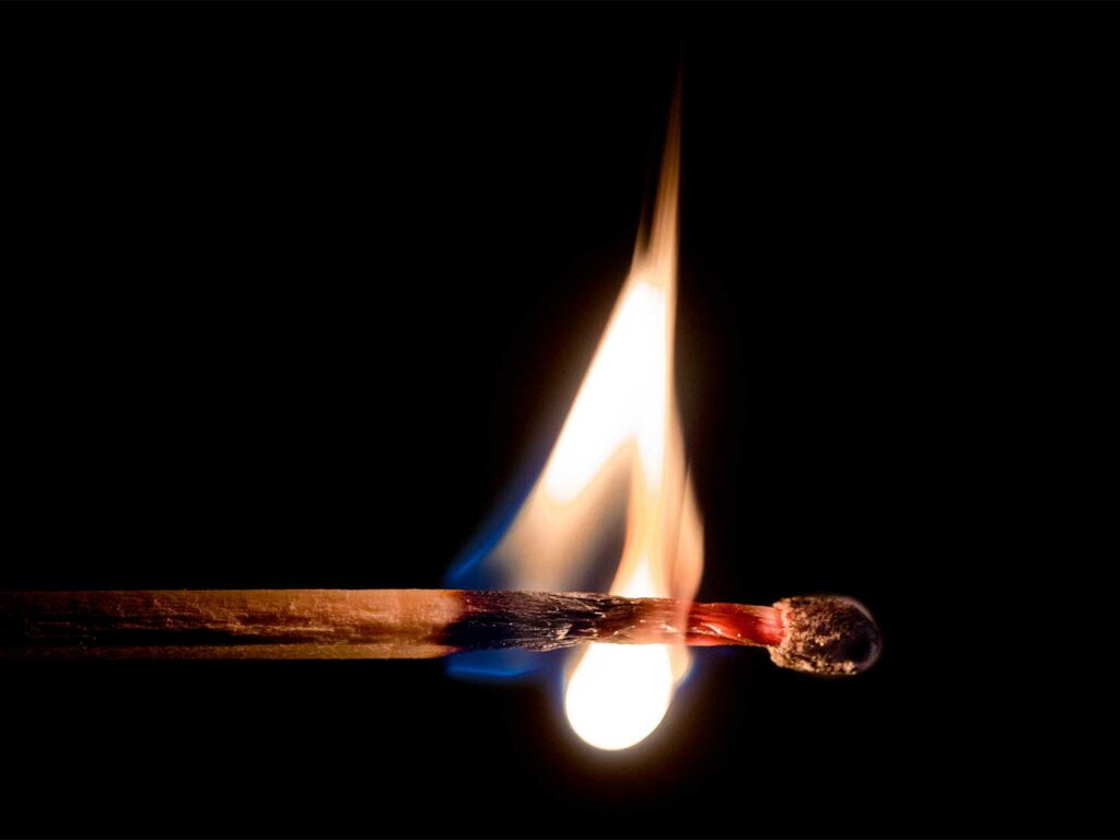 A lit match burns against a black background.
