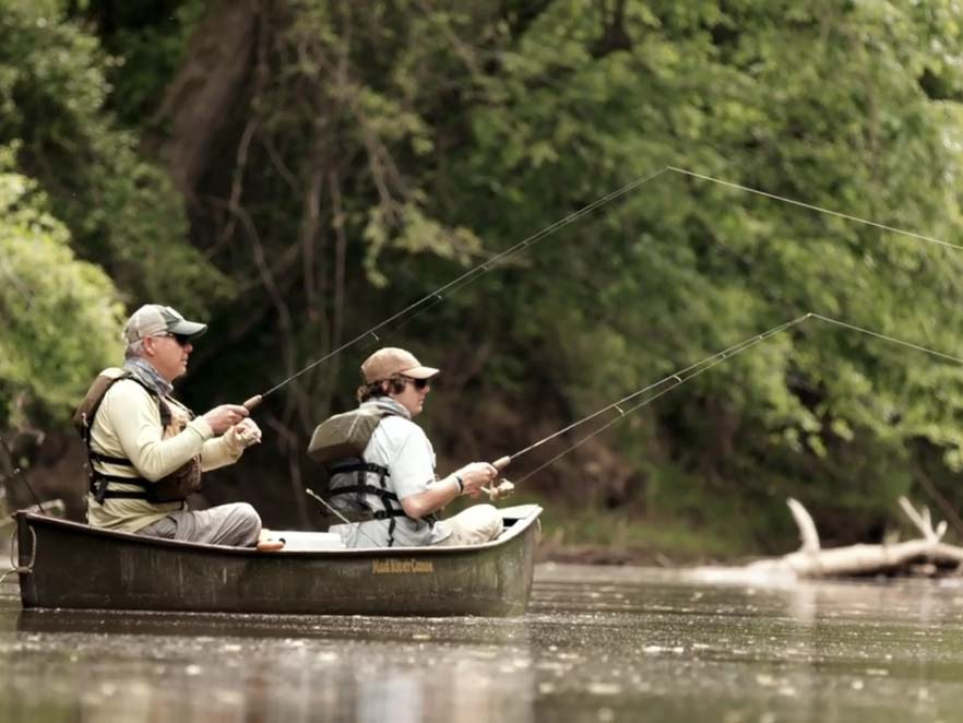 Two men fishing in a small boat on a creek.