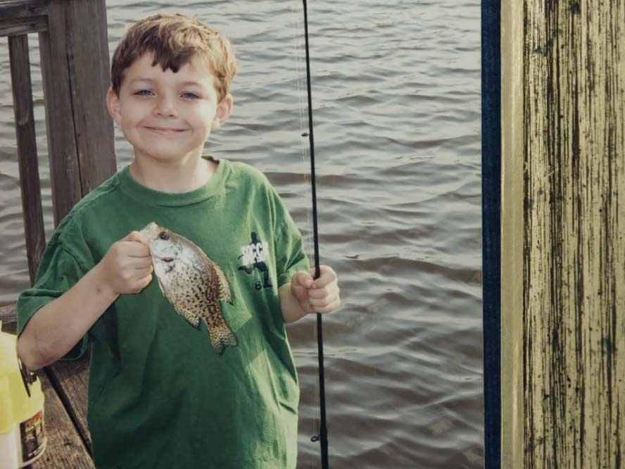 A young boy holds a fishing pole in one hand and a crappie fish in the other.