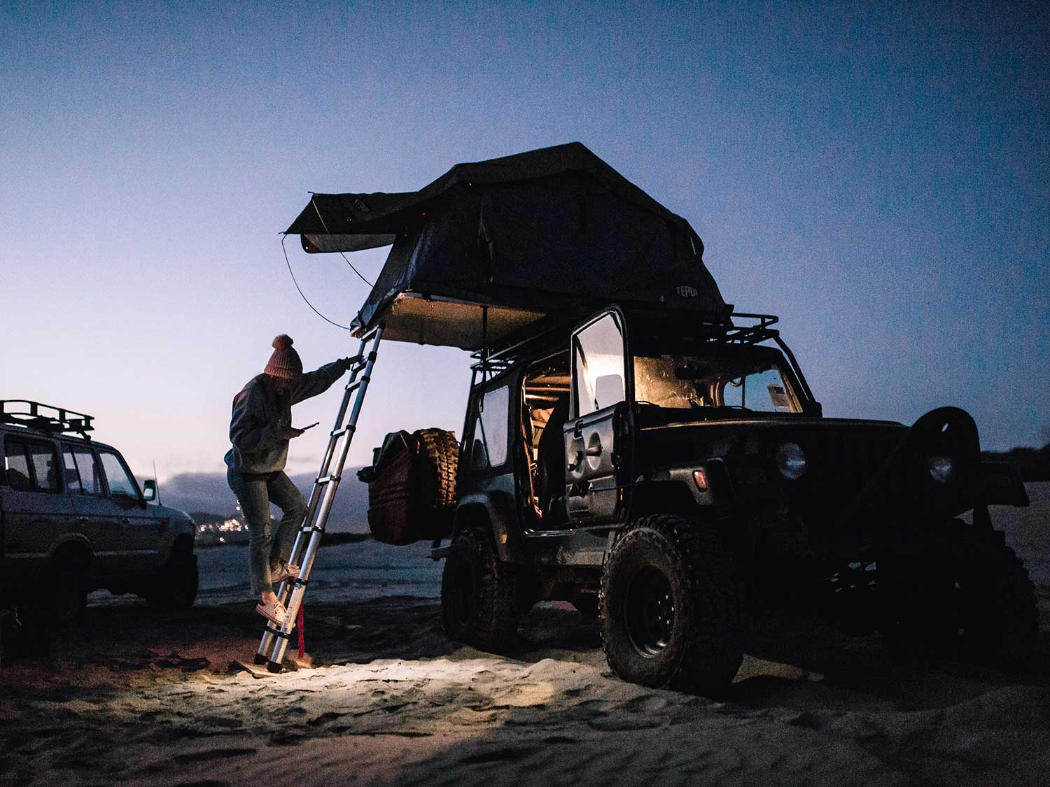 Man on ladder with overland tent.