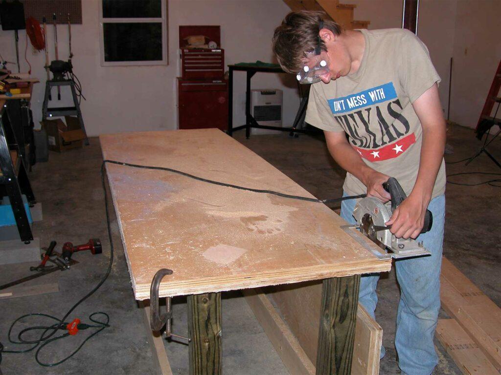 A man building a long custom table.