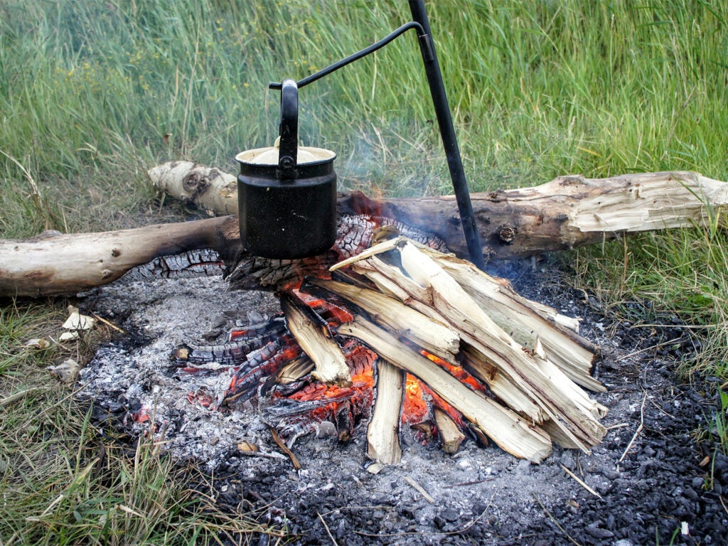 A campfire cookstove over a burning fire.