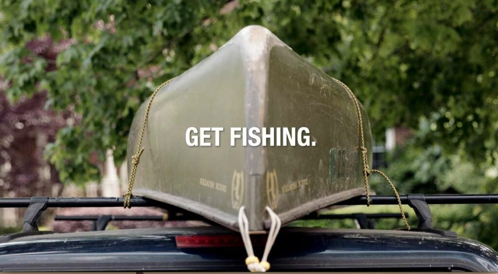 A fishing canoe tied down to a rack on top of a truck.