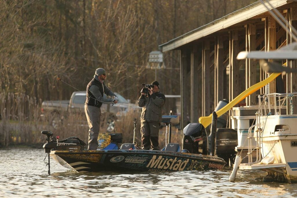 A BASS pro Brandon Lester fishes near a boathouse on a river.