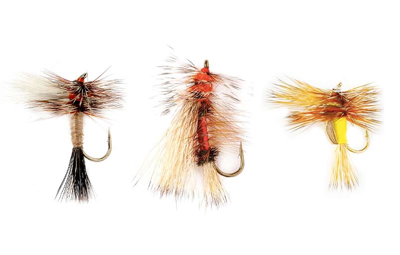 Three fly fishing lures on a white background.