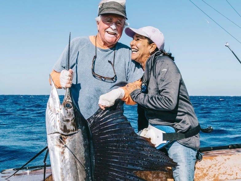 A male and female angler hold up a large sailfish.