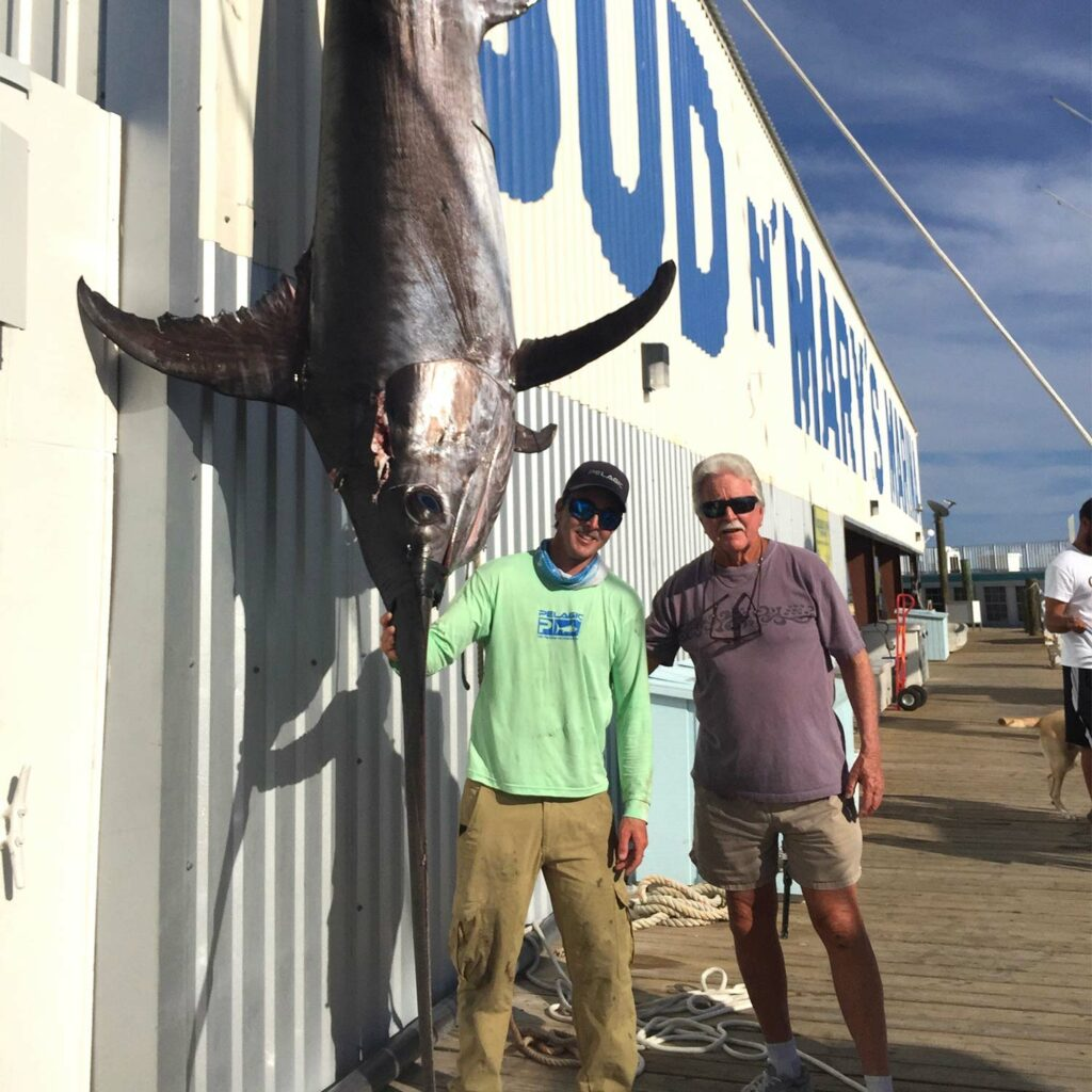 Two anglers stand beside a large swordifhs.