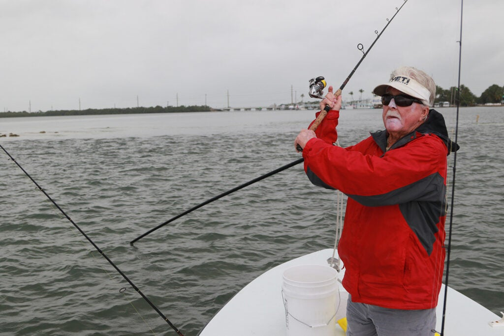A man in a red jacket casts a line in Florida Keys.