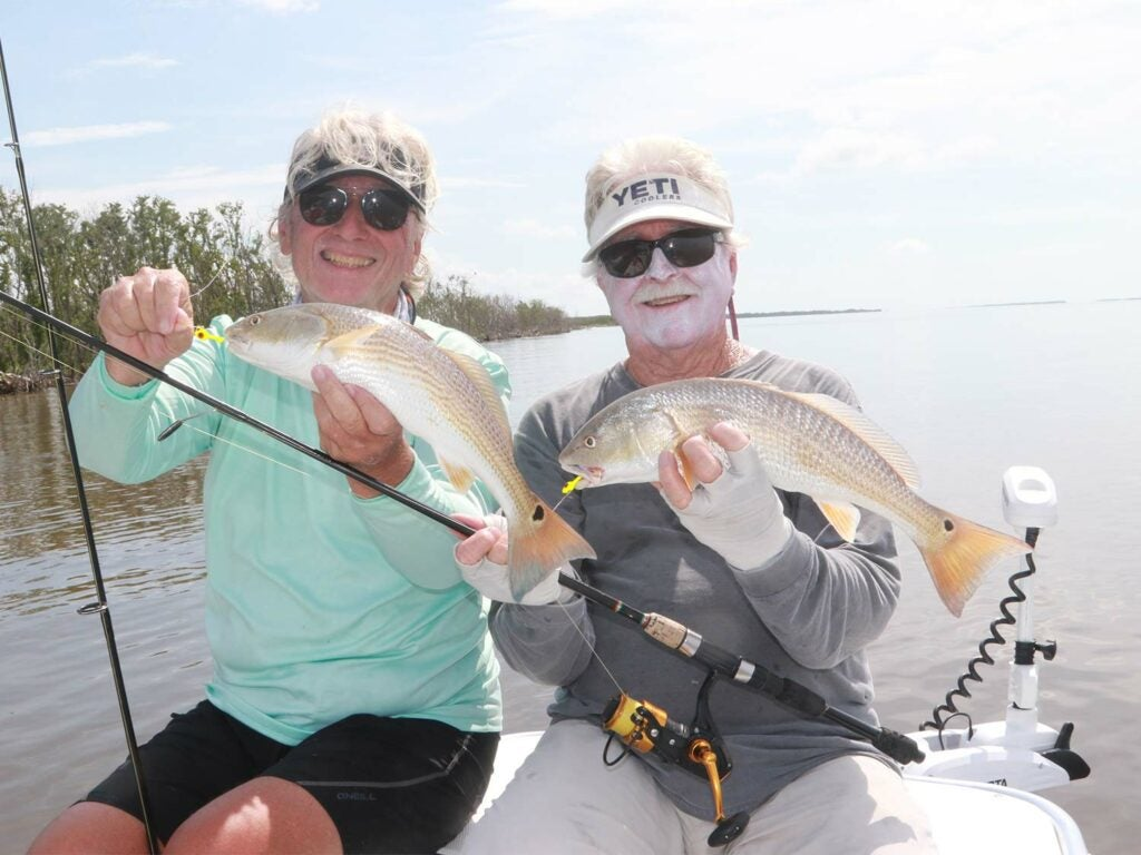 Two anglers in a boat holding up redfish.