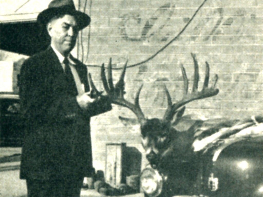 Black and white image of a man and a deer's head.