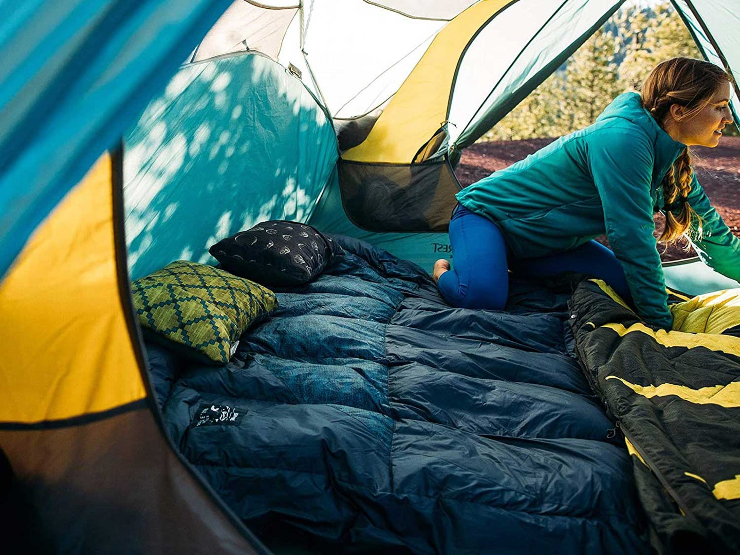 Woman in tent with sleeping bag and camping pillows.