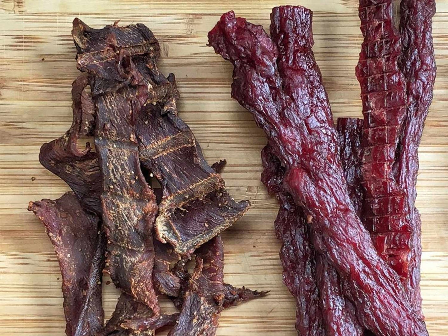 Two types of beef jerky on a cutting board.