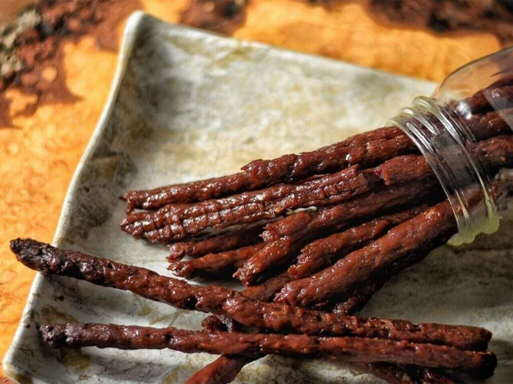 Several beef jerky sticks on a cooking sheet.