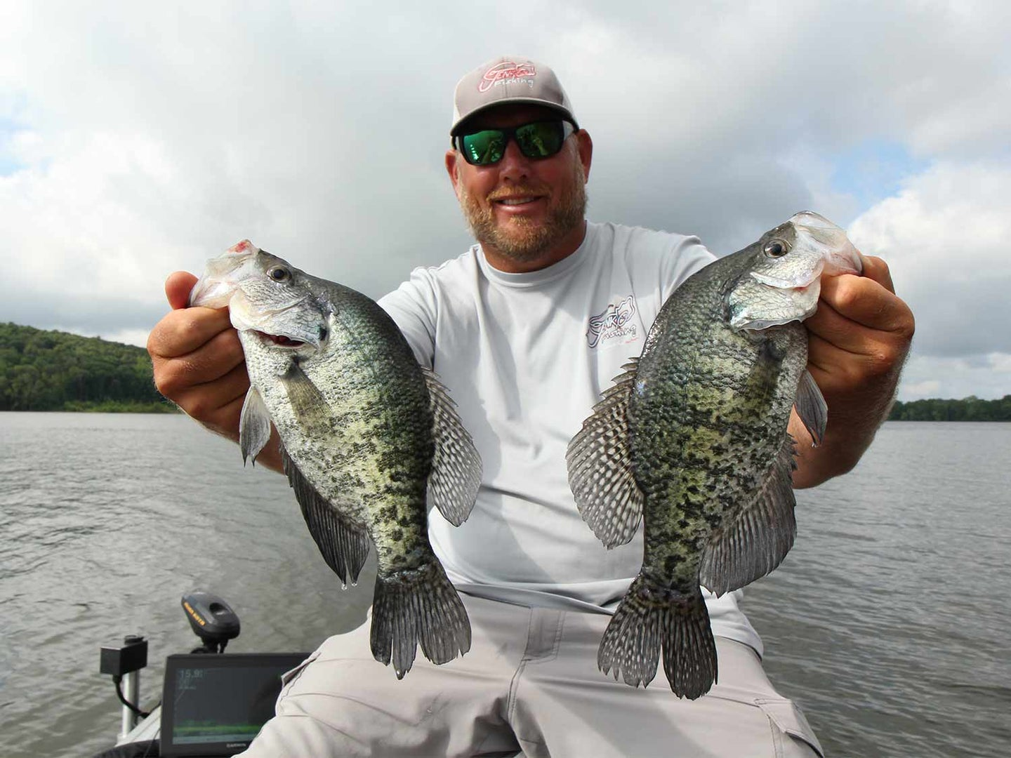 A male angler holding up two large crappie fish.
