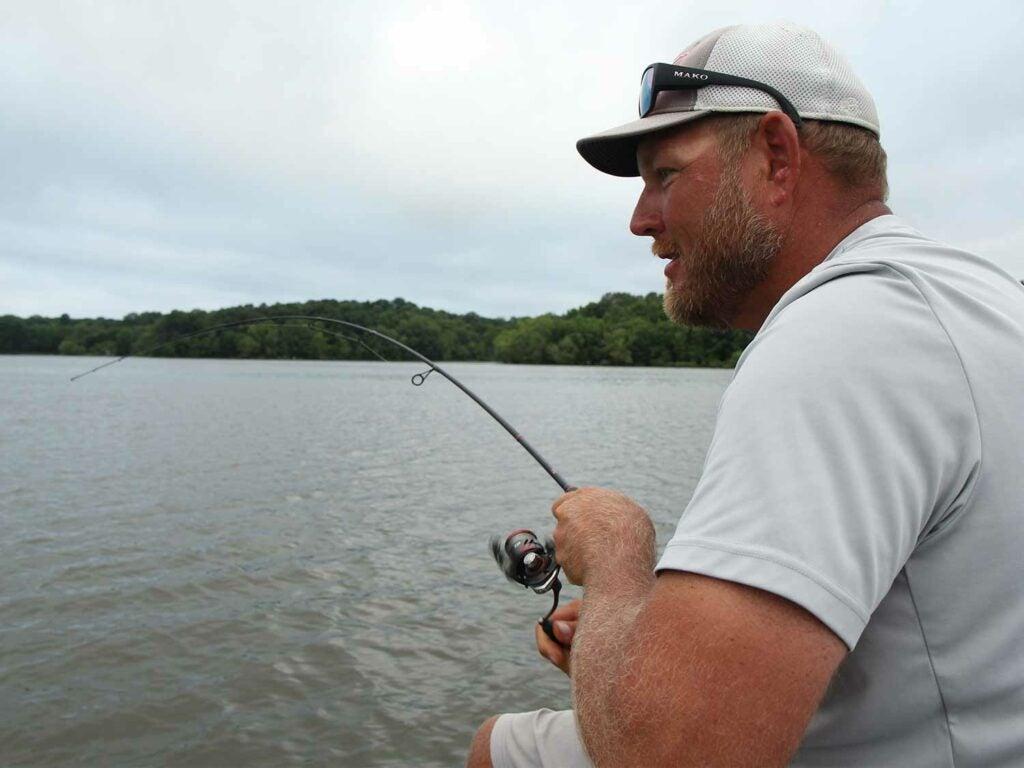 A bass fishing angler in a white shirt fishing in a lake.