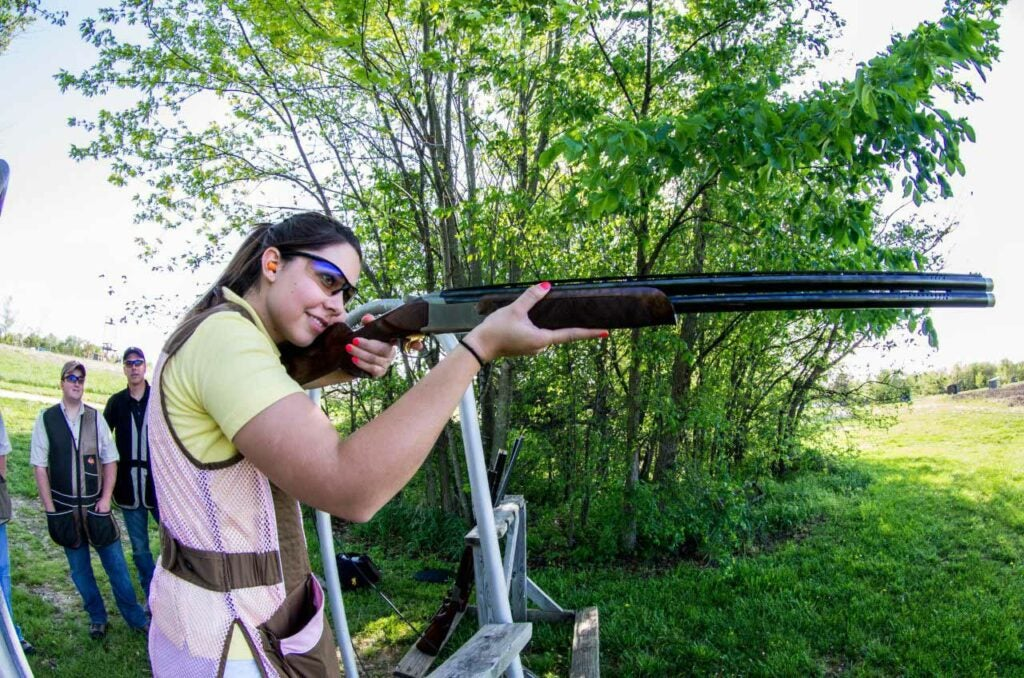 A young woman in a pink vest aims a shotgun at a shooting range.