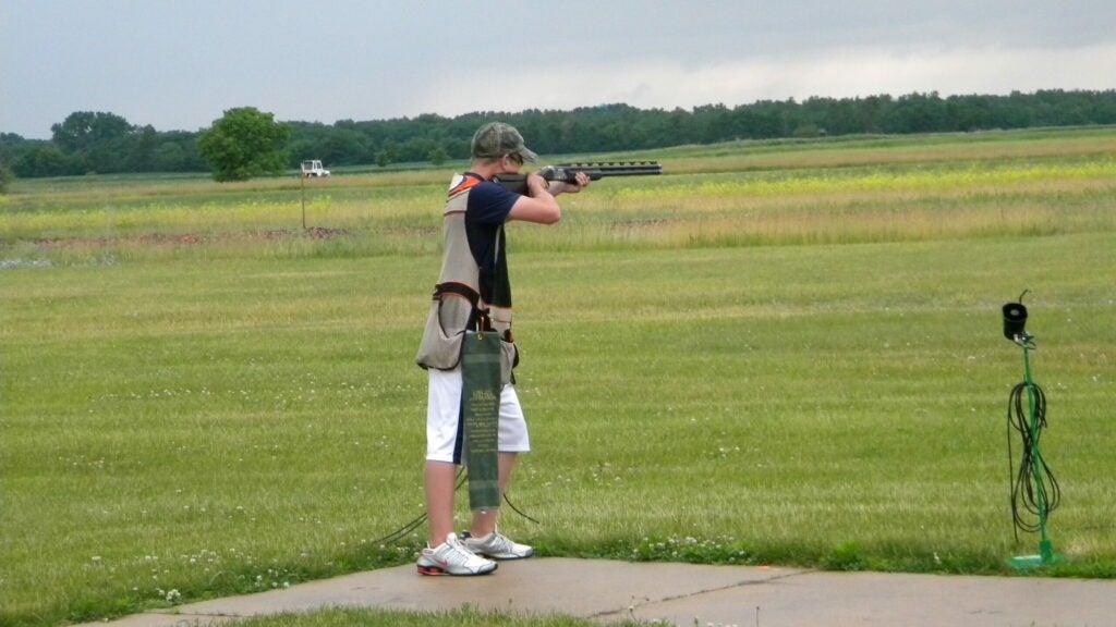 Boy holding shotgun standing on a shooting range.