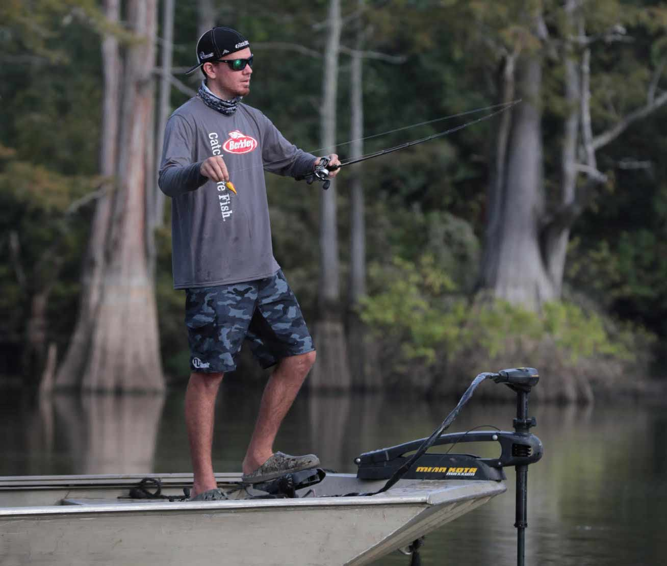 A bass angler stands at the front of a fishing boat getting ready to cast a line.